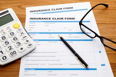 Insurance claim form with pen and calculator on wood desk - stock photo