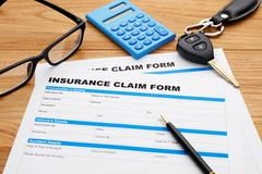 Insurance claim form with pen and car key on wood desk - stock photo