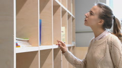 Young girl looking and finds  the book on a shelf in the library Stock Footage