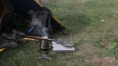 Coffee pot boiling on the hearth next to the tent Stock Footage