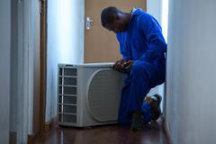 Handyman testing air conditioner Stock Photos