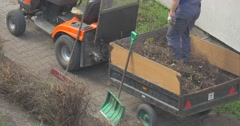 Worker Tamps Dry Grass in Trailer Small Car Shovels Are Leaned to the Vehicle Stock Footage