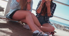 Teen girls eating hamburgers together outdoors on a summer day Stock Footage