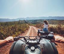 Young people on quad bikes on mountain trail - stock photo