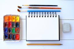 Notepad, brushes and paint on the table - stock photo