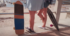 Skater girls in shorts standing at the seaside with skateboards Stock Footage