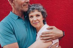 Happy mature woman embracing her husband - stock photo