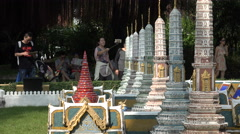 Chinese tourists look at miniature Thai temple in theme park Stock Footage