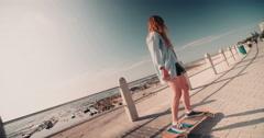 Teen skater girl riding her skateboard along the beachfront - stock footage