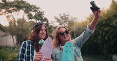 Hipster teen girls taking a selfie together with skateboards Stock Footage