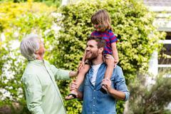 Granddad looking at son carrying grandson Stock Photos