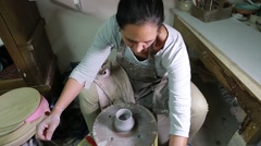 Female potter at wheel in studio ending clay work Stock Footage