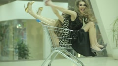 Two glamorous girls playing with a push-cart in a store Stock Footage