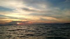 Traveling through the sea splashing water cloudy twilight sunset Stock Footage