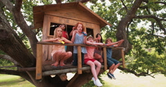 Children blowing bubbles on the porch of a wooden treehouse Stock Footage