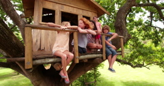 Children in a treehouse smiling together as friends Stock Footage