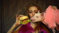 Girl feeding a piglet with a hamburger - stock footage