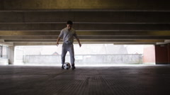 Football player doing kick ups in an urban city environment Stock Footage
