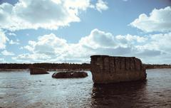 support the destroyed bridge on river against blue sky - stock photo