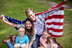 Hapy family holding american flag in the park Stock Photos