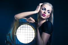 Sexy young woman with old floodlight - stock photo