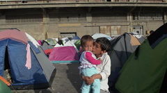 EDITORIAL: Syrian boy with little sister in her arms in a tent camp for refugees Stock Footage