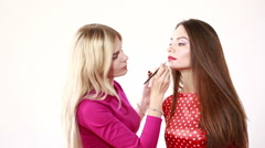 Stock Video Footage of Backstage scene: Professional Make-up artist doing glamour model makeup at work