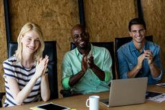 Colleagues applauding at their desk Stock Photos