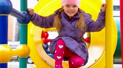 Girl playing in a yellow tube at the playground Stock Footage