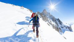 Mountaineers climb a snowy peak. - stock photo