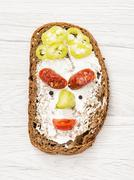 Funny face made of bread, butter, sausage, paprika, black pepper and tomato - stock photo