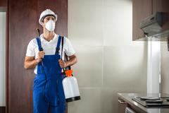 Front view of pest worker spraying in kitchen - stock photo