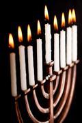 Beautiful lit hanukkah menorah on black background. Stock Photos