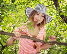 Young positive caucasian woman with stylish sunhat posing on the tree Kuvituskuvat