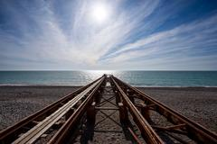 Old marine pier on sea stretching into the distance on background beautiful s - stock photo