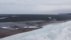 Spring ice breakup on the sea shore. White and darkened ice and open water. - stock footage