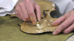 Luthier forms the harmony bar of a violin - stock footage