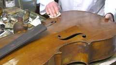 Cleaning and polishing an old cello table Stock Footage