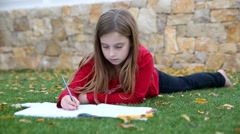 Blond kid girl maths homework on grass counting - stock footage