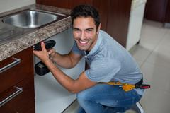 Portrait of cheerful man using cordless hand drill - stock photo