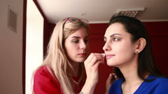 Backstage scene: Professional Make-up artist doing glamour model makeup at work - stock footage