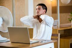 Man enjoying a breeze while using laptop Stock Photos