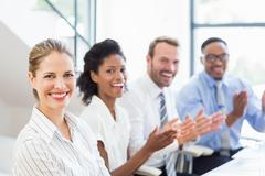 Businesspeople applauding while in a meeting Stock Photos