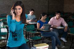 student using the cellphone on the class - stock photo