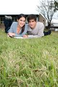 Couple lying on the grass - stock photo