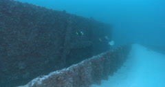Ocean scenery drifting along fishy section of wall on partially buried wreck, Stock Footage