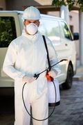 Portrait of pest control man standing next to a van - stock photo