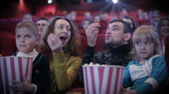 People eating popcorn and grimacing at cinema Stock Footage
