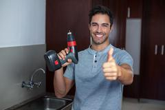 Happy man showing thumbs up while holding cordless hand drill Stock Photos
