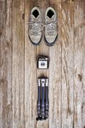 Overhead view of hiking boots, vintage camera, and tripod on a wood surface Stock Photos